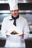 Chef holding a dish with spaghetti. In commercial kitchen Stock Image