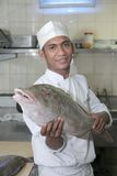 Chef holding fish at butcher Royalty Free Stock Image