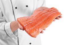 Chef holding fresh raw salmon fillet, isolated. On white Royalty Free Stock Photos