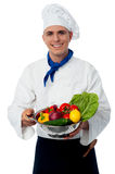 Chef holding fresh vegetables in strainer bowl Stock Photos