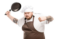 Chef holding frying pan and looking at camera isolated on white Royalty Free Stock Photography