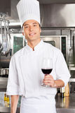 Chef Holding Glass Of Red Wine. Portrait of handsome chef holding glass of red wine in commercial kitchen Royalty Free Stock Image
