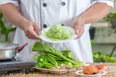 Chef holding green noodle Stock Photography