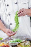 Chef holding green noodle Royalty Free Stock Images