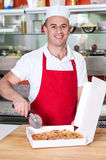 Chef holding pizza cuter, ready to cut. Stock Photos
