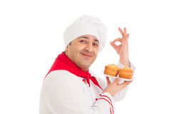 Chef holding plate with 4 muffins wearing red and white uniform Stock Photo