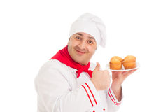 Chef holding plate with 4 muffins wearing red and white uniform Royalty Free Stock Photos