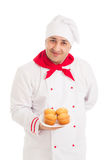 Chef holding plate with 4 muffins wearing red and white uniform Stock Image