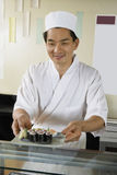 Chef Holding Plate Of Sushi In Restaurant. Smiling male chef holding plate of sushi in the restaurant stock photo