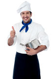 Chef holding a pot showing the ok hand sign. Smiling young chef holding pan and gesturing ok Royalty Free Stock Image
