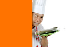 Chef holding raw fish on a green plate. With orange blank space isolated on white background Royalty Free Stock Photography