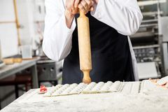 Chef Holding Rolling Pin While Standing At Counter Lizenzfreie Stockfotos