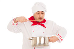 Chef holding saucepan weraing red and white uniform tasting food Royalty Free Stock Images