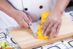 Chef holding slice of yellow bell pepper Stock Photo