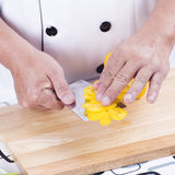 Chef holding slice of yellow bell pepper Stock Images