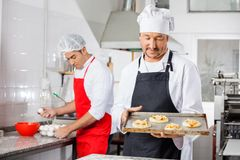 Chef Holding Small Pizzas On Tray With Colleague Royalty Free Stock Photography