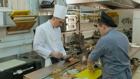 Chef holding tablet and instructing his trainee how to chop mushroom stock footage