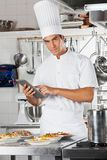 Chef-Holding Tablet With-Teigwaren-Teller am Zähler Lizenzfreie Stockfotografie
