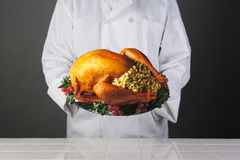 Chef Holding Thanksgiving Turkey on Platter. Closeup of a chef holding a platter with a Thanksgiving Turkey with all the trimmings. Horizontal format over a royalty free stock photos