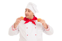 Chef holding two muffins wearing red and white uniform Royalty Free Stock Photography
