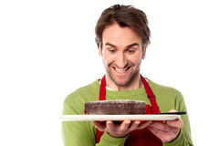 Chef holding yummy chocolate cake. Male chef looking at cake excitedly Stock Photography