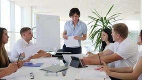 Chef- holdings commerciële vergadering van partners met documenten bij lijst in modern bureau stock footage