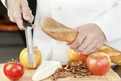 Chef Holds Bread Knife. Close-up of a chef holding a bread knife over a bamboo cutting board of apples, brie, a baguette and pecans Royalty Free Stock Image