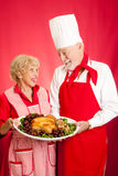 Chef and Homemaker with Holiday Dinner. Chef and homemaker collaborated on making a delicious holiday turkey dinner. Red background royalty free stock image