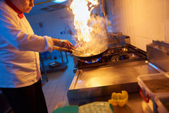 Chef in hotel kitchen prepare food with fire Stock Photo