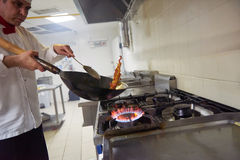 Chef in hotel kitchen prepare food with fire Stock Photos