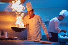 Chef in hotel kitchen prepare food with fire. Chef in hotel kitchen prepare vegetable  food with fire Royalty Free Stock Photography
