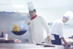 Chef in hotel kitchen prepare food with fire Royalty Free Stock Image