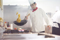 Chef in hotel kitchen prepare food with fire Stock Images