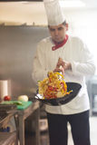 Chef in hotel kitchen prepare food with fire Stock Photography