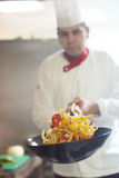 Chef in hotel kitchen prepare food with fire Royalty Free Stock Photography
