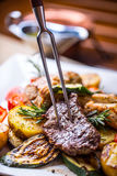 Chef in hotel or restaurant kitchen cooking only hands. Prepared beef steak with vegetable decoration Stock Photos