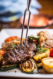 Chef in hotel or restaurant kitchen cooking only hands. Prepared beef steak with vegetable decoration Stock Photography