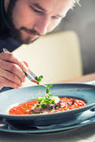Chef in hotel or restaurant kitchen cooking, only hands. He is working on the micro herb decoration. Preparing tomato soup Royalty Free Stock Image