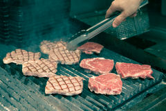 Chef in hotel or restaurant kitchen grilling pork for dinner Royalty Free Stock Image