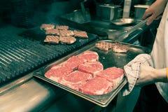 Chef in hotel or restaurant kitchen grilling pork for dinner Stock Photos