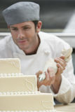 Chef Icing Wedding Cake. Male chef icing wedding cake in kitchen royalty free stock photo