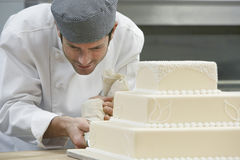 Chef Icing Wedding Cake. Male chef icing wedding cake in kitchen Stock Image