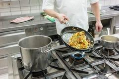 Chef im Restaurant, das Gemüse in der Wanne brät Lizenzfreies Stockbild