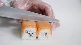 Chef im Restaurant, das Sushirollengesundes Lebensmittel zubereitet und schneidet Stockbild