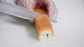 Chef im Restaurant, das Sushirollengesundes Lebensmittel zubereitet und schneidet Lizenzfreie Stockbilder