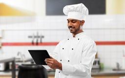 Chef indien avec le PC de comprim? ? la cuisine de restaurant photo stock