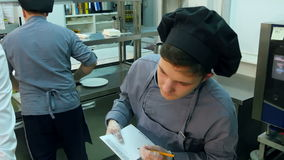 Chef instructing trainee how to cook fish while he is taking notes. Professional shot on Lumix GH4 in 4K resolution. You can use it e.g. in your commercial stock footage