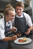 Chef Instructing Trainee In Restaurant Kitchen Stock Image