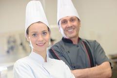Chef instructing trainee in restaurant kitchen stock photos