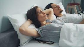 Chef irrité de bâche de femme avec l'oreiller quand ami ronflant dans le sommeil dans le lit banque de vidéos
